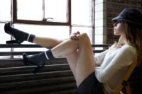 fashion-editorial-image-woman-wearing-hat-showing-legs-sitting-near-window